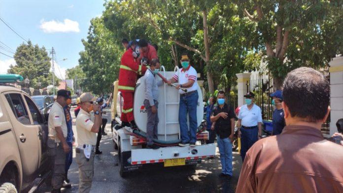 Gubernur Gorontalo Rusli Habibie memegang Stik Sprayer saat lakukan penyemprotan disinfektan. (Foto : Istimewa)