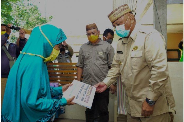 Gubernur Gorontalo Rusli Habibie saat memberikan bantuan ke warga, (Foto : Humas Pemprov Gorontalo)