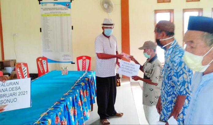 Kepala Desa Sonuo, Harsono Puasa saat proses memberikan uang Bantuan Langsung Tunai (BLT). (Rabu, 5/5/2021).